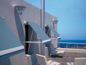 Zonas de sombra y un toque de color en una terraza al mar